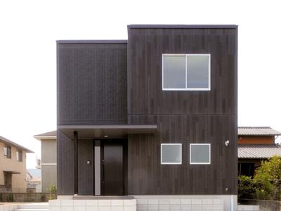 木目調と石張り調で際立つダークブラウンのシンプルデザイン住宅